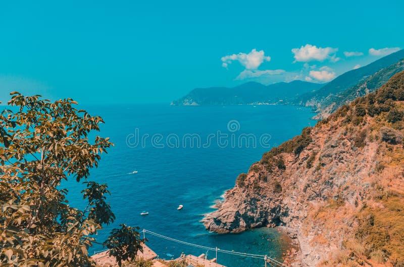 Een prachtig landschap van een zee omringd door grote rotsbergen onder de troebele hemel op 5 Terre, Italië stock foto's