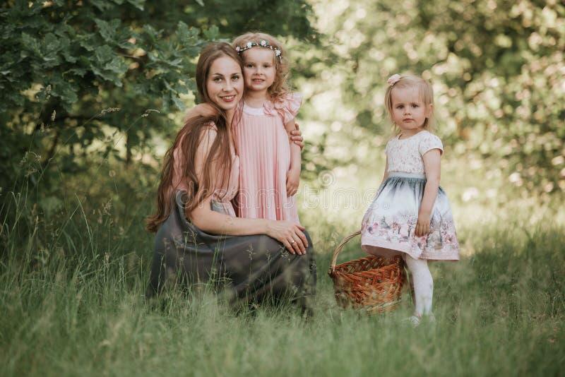 Een prachtig portret van mamma met twee dochters in het park Moeder en twee dochters het wervelen stock afbeelding