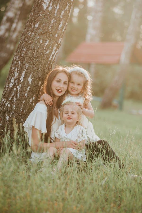 Een prachtig portret van mamma met twee dochters in het park Moeder en twee dochters het wervelen stock foto