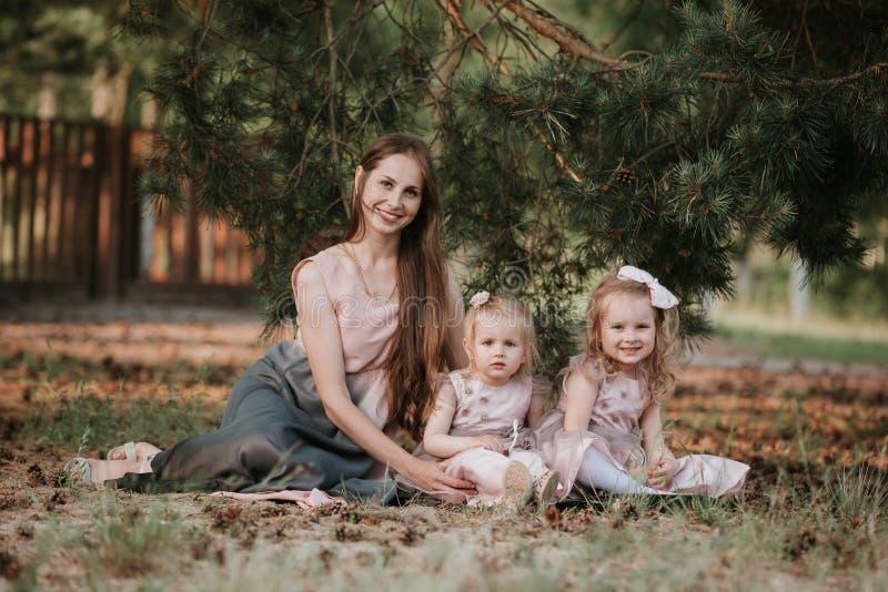 Een prachtig portret van mamma met twee dochters in het park Moeder en twee dochters het wervelen stock fotografie