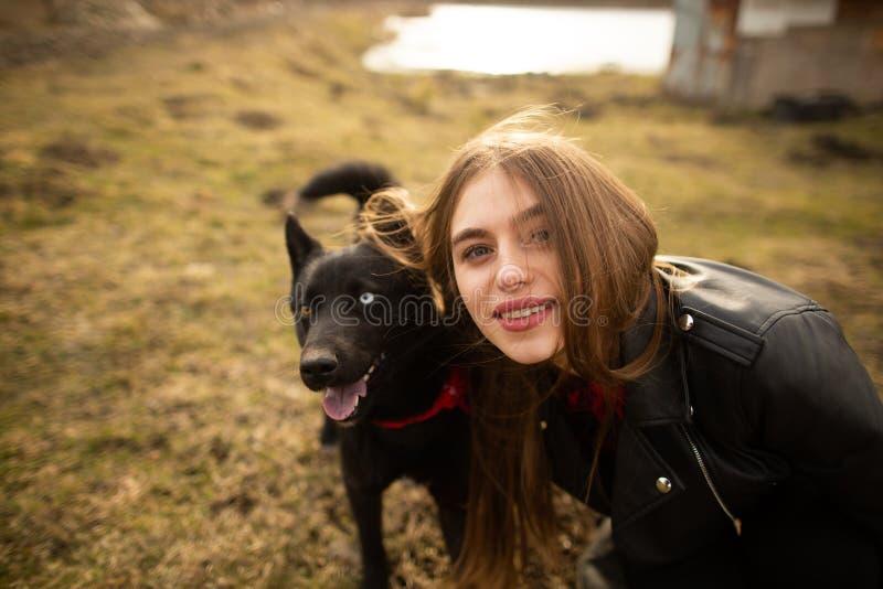 Een prachtig portret van een meisje en haar hond met kleurrijke ogen De vrienden stellen op de kust van het meer stock fotografie