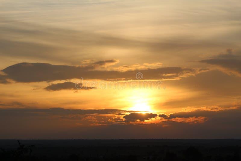 Een prachtige warme avondzonsondergang met een bewolkte hemel stock foto