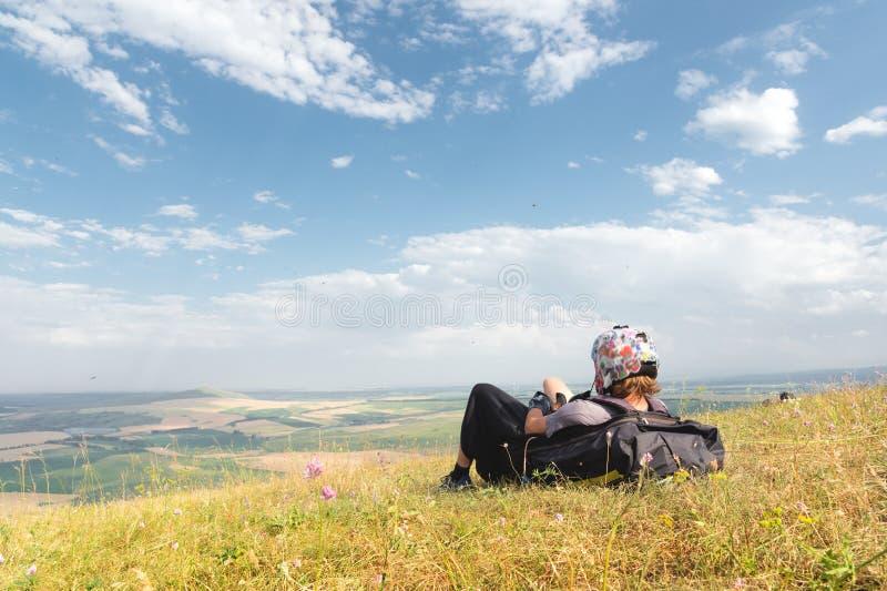 Een professioneel glijscherm in volledig toestel en een helm ligt en rust hoog op het gras in de bergen bekijkend royalty-vrije stock afbeelding