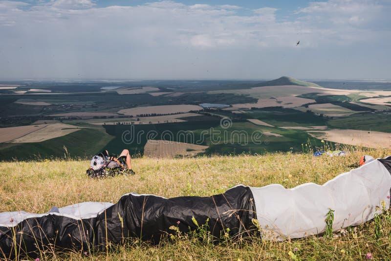 Een professioneel glijscherm in volledig toestel en een helm ligt en rust hoog op het gras in de bergen bekijkend stock afbeelding
