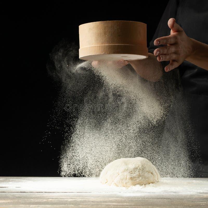 Een professionele kok in een professionele keuken bereidt bloemdeeg voor om bio-Italiaanse deegwaren te maken concept aard, Itali royalty-vrije stock afbeeldingen