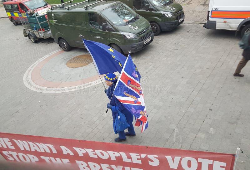 Een protesteerder anti-Brexit met zowel de Britse vlaggen van de EU als royalty-vrije stock foto's