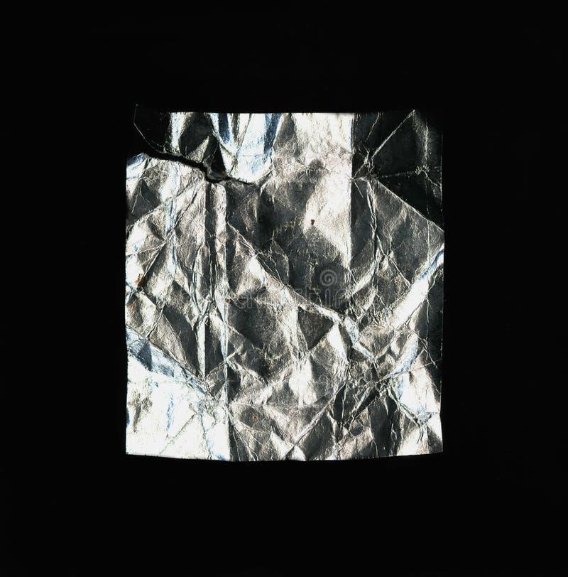 Een rechthoekig stuk van verfrommelde folie Geïsoleerd op een zwarte achtergrond royalty-vrije stock foto's