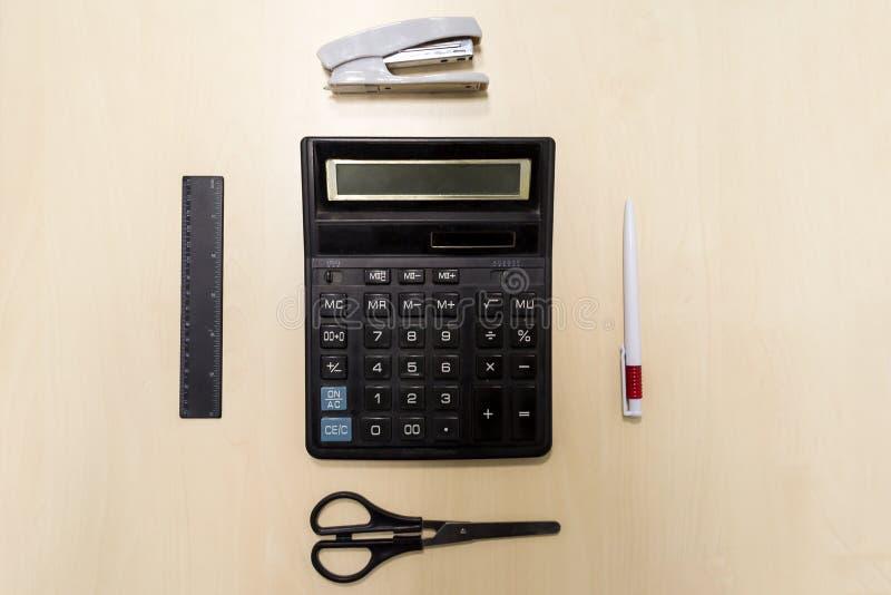 Een reeks bureauhulpmiddelen die uit een calculator, pen, nietmachine bestaan, stock foto