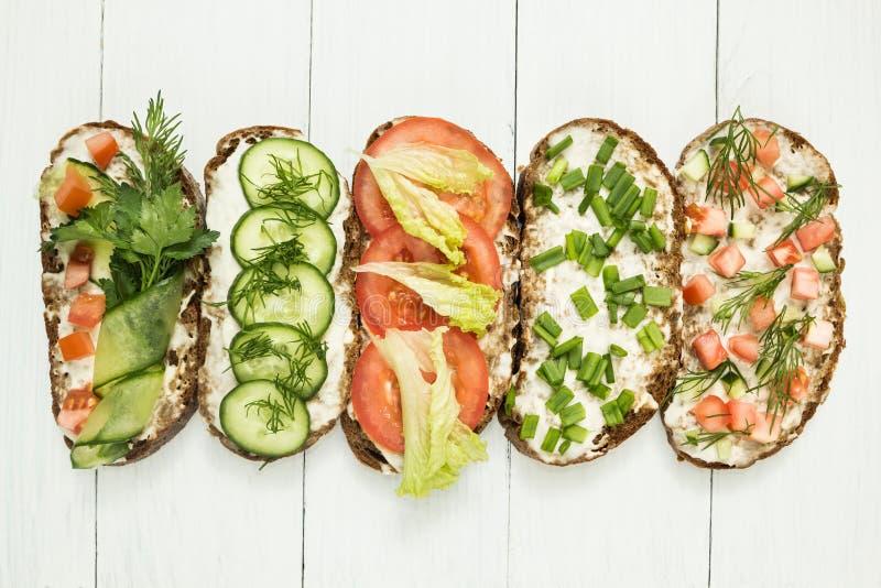 Een reeks eigengemaakte vegetarische sandwiches op een witte achtergrond Hoogste mening, vlakke samenstelling royalty-vrije stock foto's