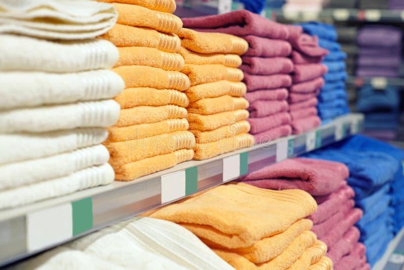 Een reeks gekleurde handdoeken op een plank in een opslag stock foto