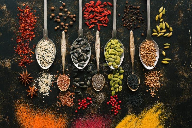 Een reeks gevarieerde zaden en kruiden in lepels op een donkere achtergrond De hoogste vlakke mening, legt Multicolored kruiden stock foto