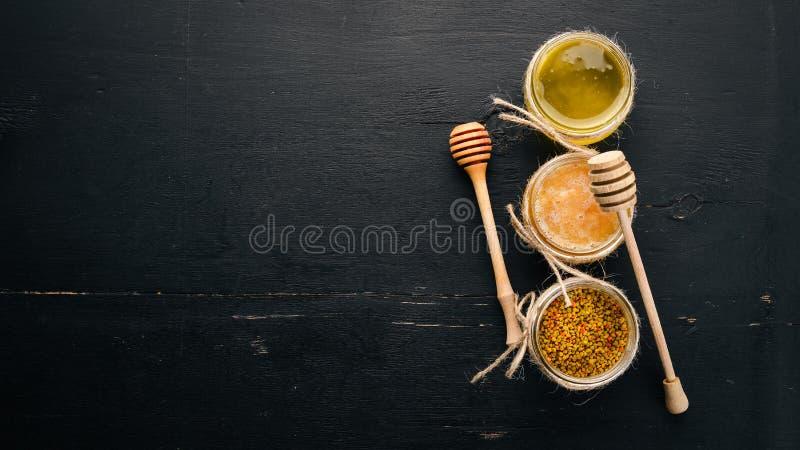 Een reeks honing en bijenproducten Honing in honingraat Op een zwarte houten achtergrond Vrije ruimte voor tekst stock foto's