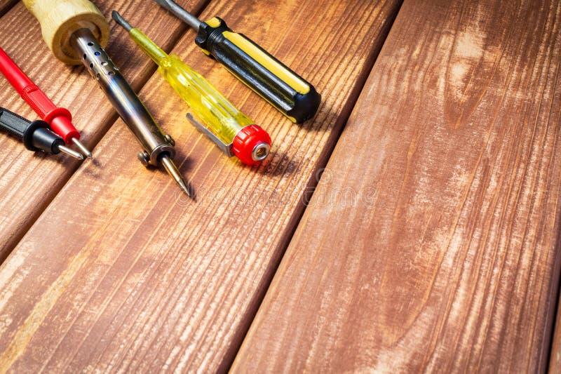 Een reeks hulpmiddelen om elektronika, op houten achtergrond te onderhouden stock afbeelding