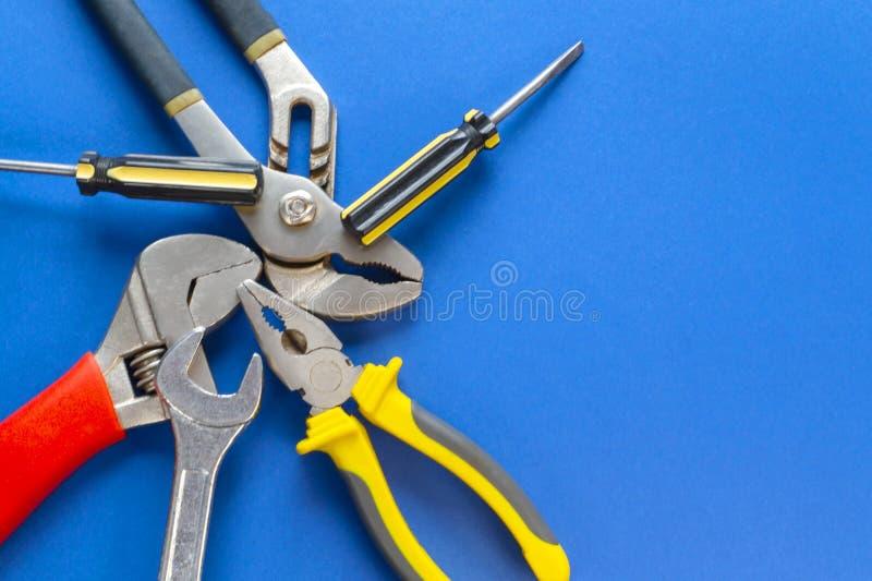 Een reeks hulpmiddelen voor loodgieterswerk, op een blauwe achtergrond wordt geïsoleerd die stock afbeeldingen