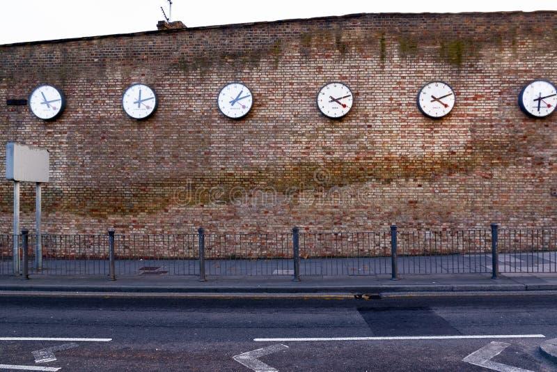 Een reeks klokken die The Times in grote steden registreren stock foto's