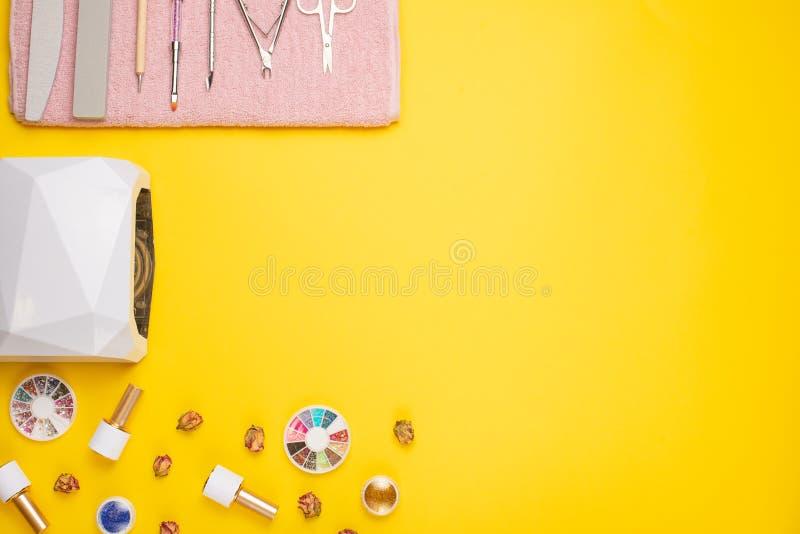 Een reeks kosmetische hulpmiddelen voor manicure en pedicure op een purpere achtergrond Gelpoetsmiddelen, nagelvijlen en tangen e royalty-vrije stock foto's