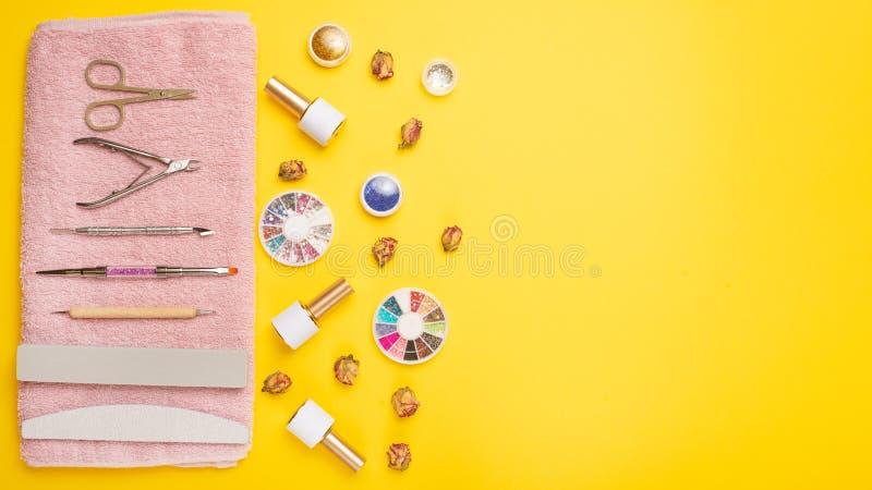 Een reeks kosmetische hulpmiddelen voor manicure en pedicure op een purpere achtergrond Gelpoetsmiddelen, nagelvijlen en tangen e royalty-vrije stock fotografie