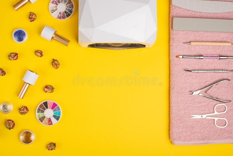 Een reeks kosmetische hulpmiddelen voor manicure en pedicure op een purpere achtergrond Gelpoetsmiddelen, nagelvijlen en tangen e stock fotografie