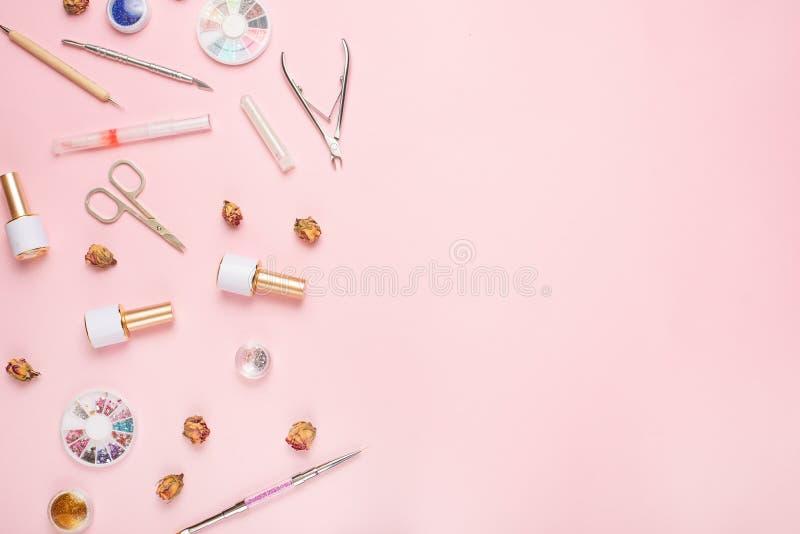 Een reeks kosmetische hulpmiddelen voor manicure en pedicure op een roze achtergrond Gelpoetsmiddelen, nagelvijlen en tangen en h stock afbeelding