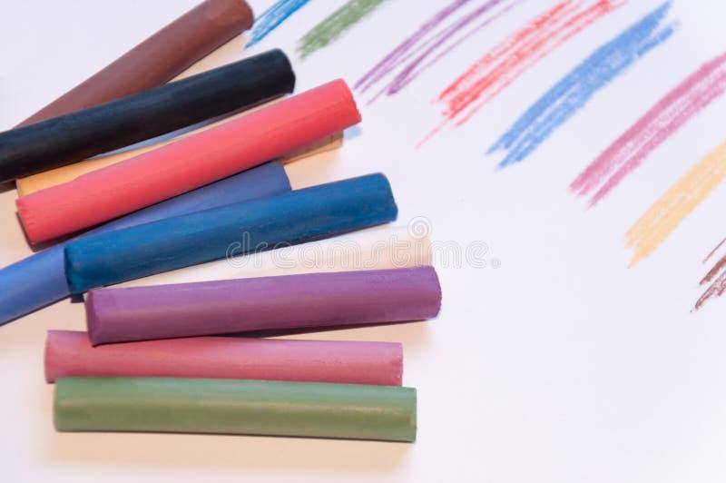 Een reeks multicolored pastelkleurpotloden op een lichte die achtergrond met een sleep naast het wordt getrokken Selectieve nadru royalty-vrije stock fotografie
