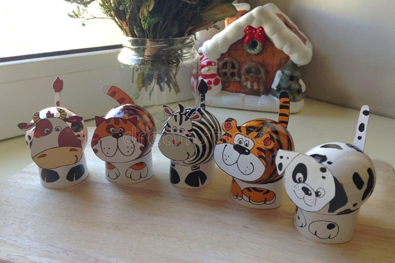 Een reeks paaseieren in de vorm van dieren op houten raad Op de achtergrond een boeket van bloemen in vaas en een huiscijfer stock fotografie