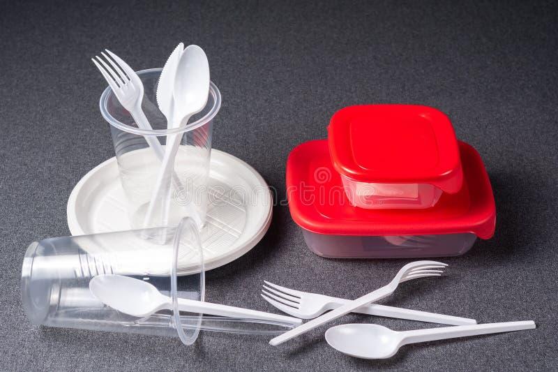 Een reeks plastic werktuigen Plastic koppen, platen, vorken, lepels en plastic containers op een grijze achtergrond Tegen plastie stock afbeelding
