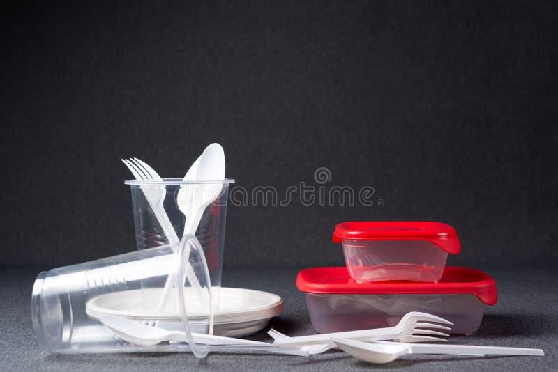 Een reeks plastic werktuigen Plastic koppen, platen, vorken, lepels en plastic containers op een grijze achtergrond Tegen plastie royalty-vrije stock afbeelding