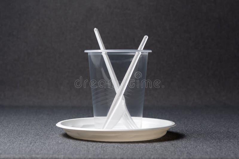 Een reeks plastic werktuigen Plastic koppen, platen, vorken, lepels en plastic containers op een grijze achtergrond Tegen plastie stock foto's
