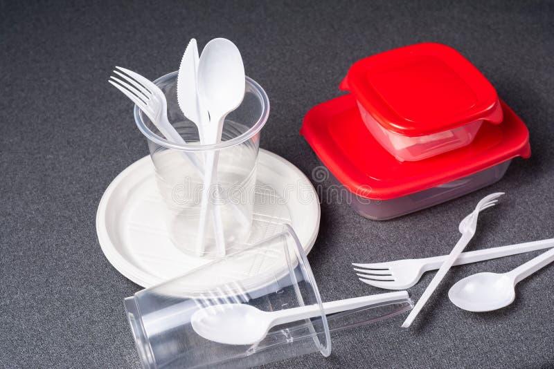 Een reeks plastic werktuigen Plastic koppen, platen, vorken, lepels en plastic containers op een grijze achtergrond Tegen plastie stock foto