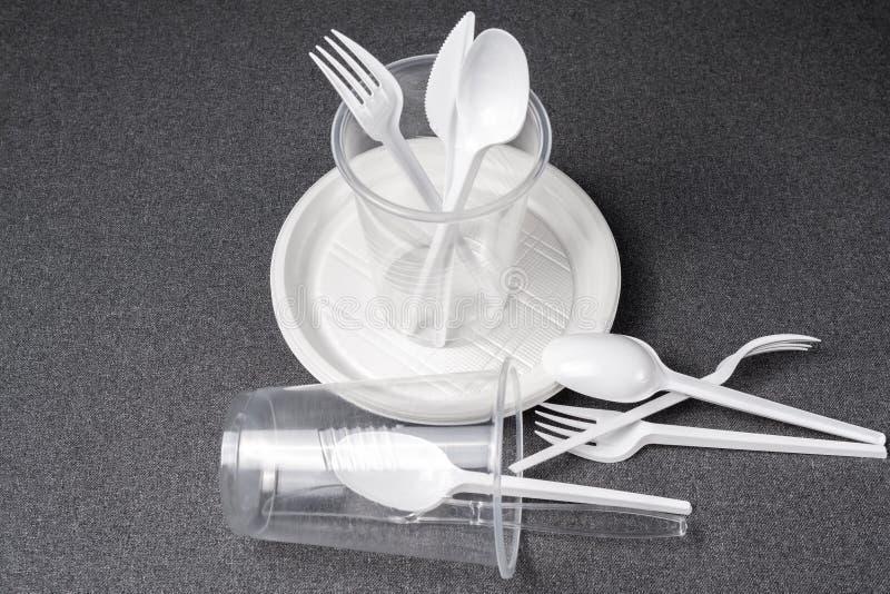 Een reeks plastic werktuigen Plastic koppen, platen, vorken, lepels en plastic containers op een grijze achtergrond Tegen plastie stock fotografie