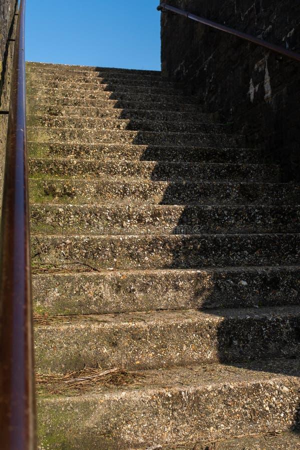 Een reeks ruwe concrete stappen die van de straat, de helft leiden stappen is in een diepe schaduw stock foto