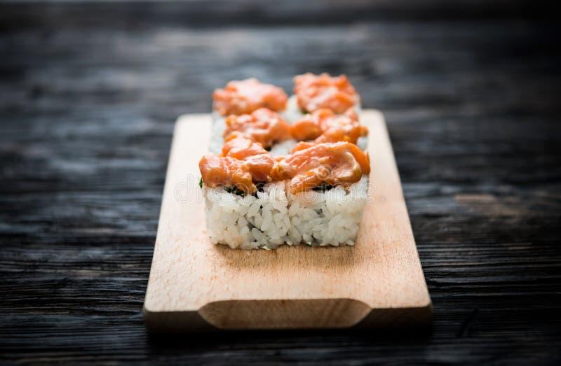 Een reeks sushi rolt met zalmbovenste laagje op houten raad stock foto's