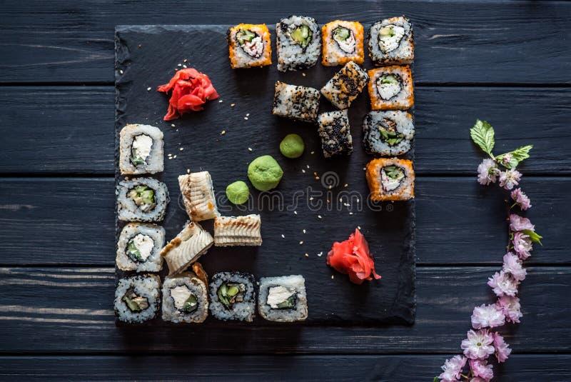 Een reeks sushi, sakura op een zwarte houten achtergrond royalty-vrije stock afbeelding