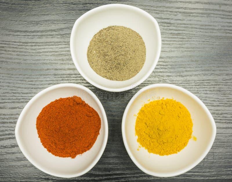 Een reeks van drie witte kommen met kruiden - peper, paprika en kerrie Mening van hierboven royalty-vrije stock fotografie