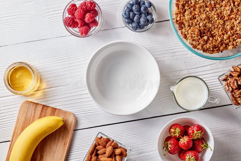 Een reeks van granolaingrediënten, banaan, honing, melk, bessen en een lege plaat voor een gezond ontbijt stap voor stap royalty-vrije stock foto's