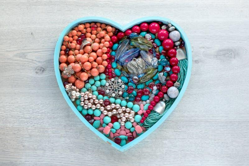 Een reeks van juwelen voor vrouwen op een houten dienblad in de vorm van een hart royalty-vrije stock afbeelding