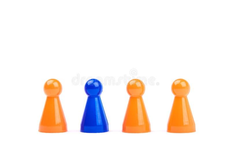 Een reeks van oranje spelstukken en één verschillend en uitzonderlijk blauw die cijfer als leider of werkgever, op een witte acht stock fotografie