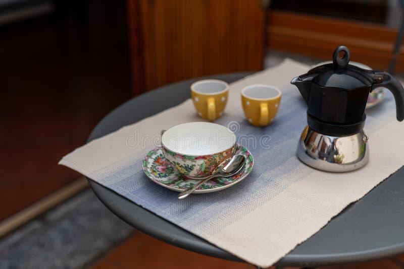 Een reeks verfraaide die koffiekoppen met coffemaker, op een lijst voor ontbijt wordt geplaatst, binnenlands ontwerp op een balko stock foto