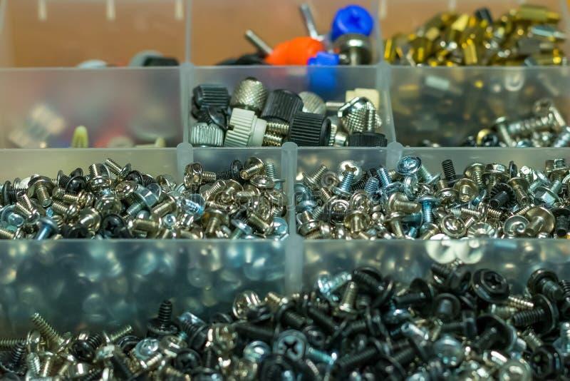 Een reeks verschillende bouten, noten voor een computer in een doos stock afbeelding