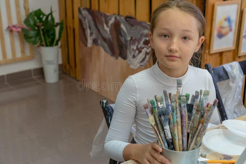 Een reeks verschillende kleurenborstels in de handen van het meisje Binnenland van de kunstacademie voor tekeningskinderen Creati royalty-vrije stock foto