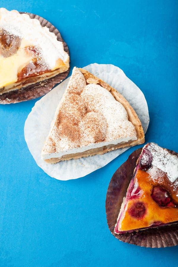 Een reeks zoete stukken van cake op een blauwe achtergrond stock foto