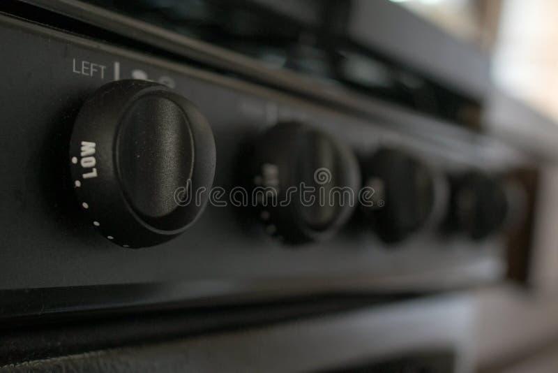 Een reeks zwarte fornuisknoppen met het witte schrijven wacht in een kampeerauto in dagtijd stock foto
