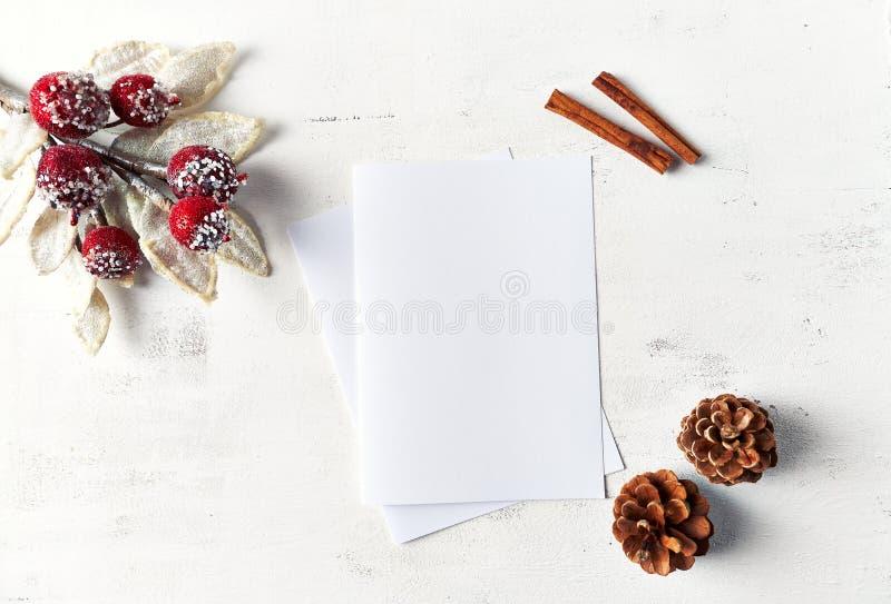 Een regeling van Kerstmisdecoratie en lege document kaarten op witte houten achtergrond flatlay De ruimte van het exemplaar stock afbeelding