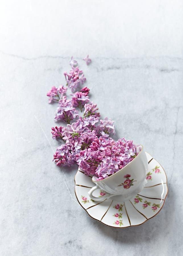 Een regeling van lilac bloemen en een uitstekende theekop stock afbeeldingen