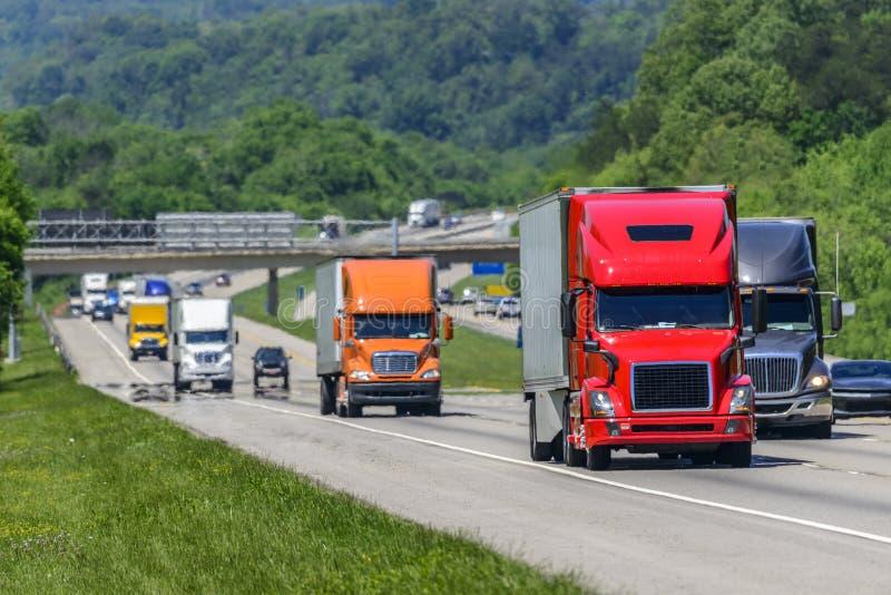 Een regelmatige stroom van semis leidt de manier onderaan een bezige weg tusen staten in Tennessee stock foto