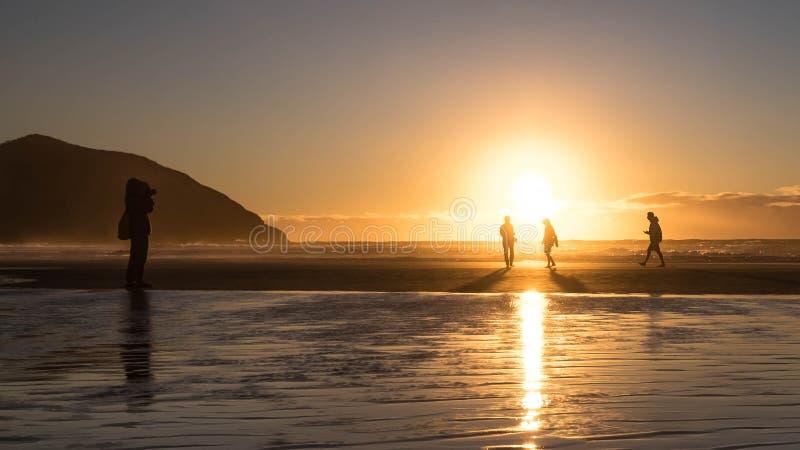 Een reisfotograaf die foto's van mensen op het strand schieten stock afbeeldingen