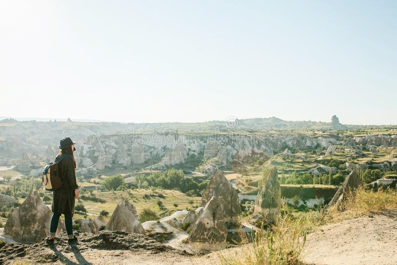 Een reiziger in een hoed met een rugzak bevindt zich op een berg en bekijkt een mooie mening in Cappadocia in Turkije Reis stock foto