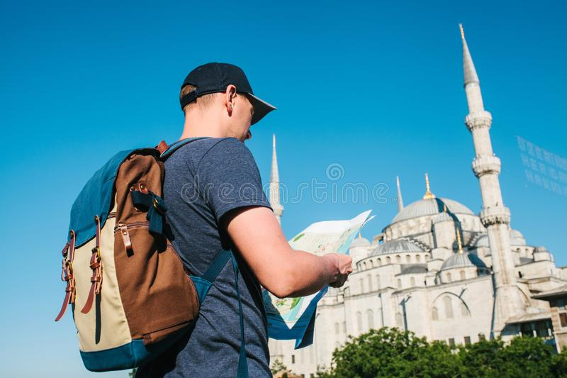 Een reiziger in een honkbal GLB met een rugzak bekijkt de kaart naast de blauwe moskee - het beroemde gezicht van stock afbeelding