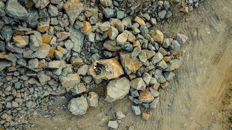 Een reiziger legt op een grote die steen door heel wat stenen in de zomer wordt omringd Een mens met een rugzak in borrels en royalty-vrije stock foto's