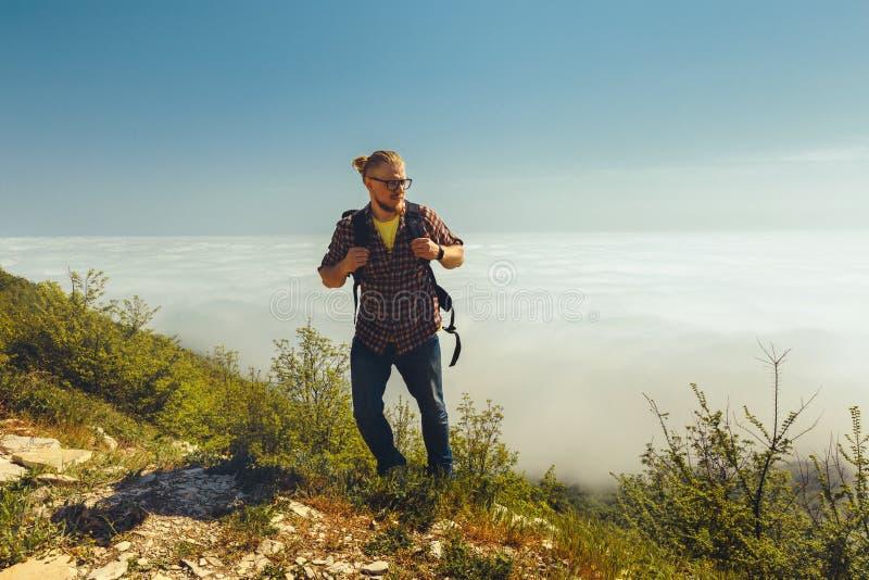 Een reizigersmens beklimt tot de bovenkant van een berg tegen een achtergrond van wolken op een zonnige dag Reislevensstijl stock afbeelding